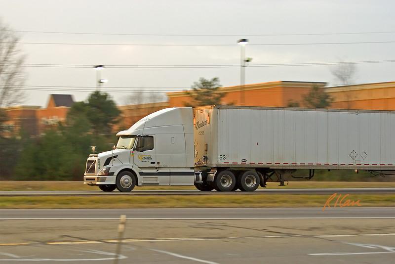 Bulk hauler freight truck: Volvo long hauler tractor and trailer heading South on US 23 in December sunset. Ann Arbor, MI 2004.