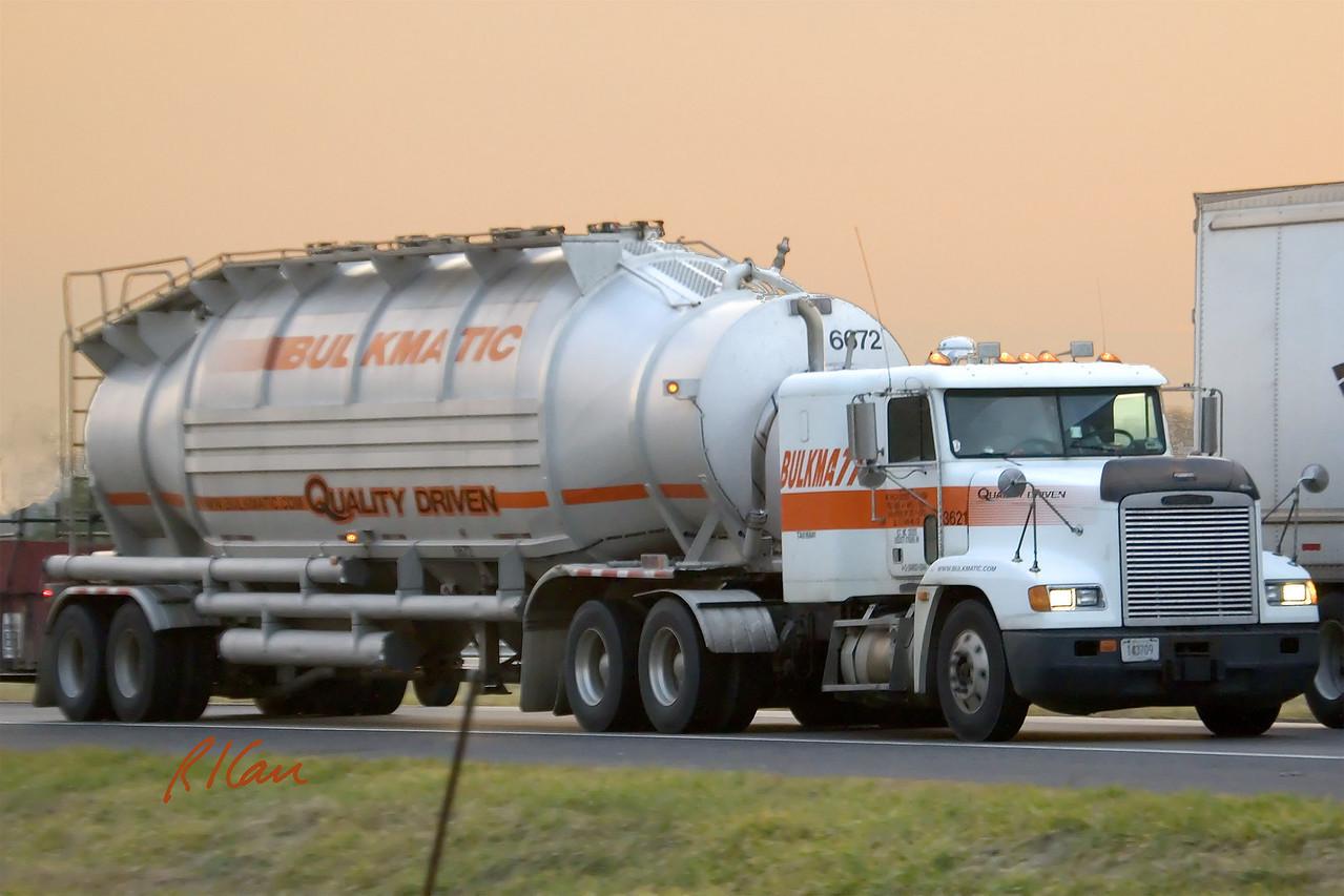 Bulk hauler freight truck: Freightliner tractor pulls bulk haul tank trailer on US 23 in December sunset. Ann Arbor, MI 2004.