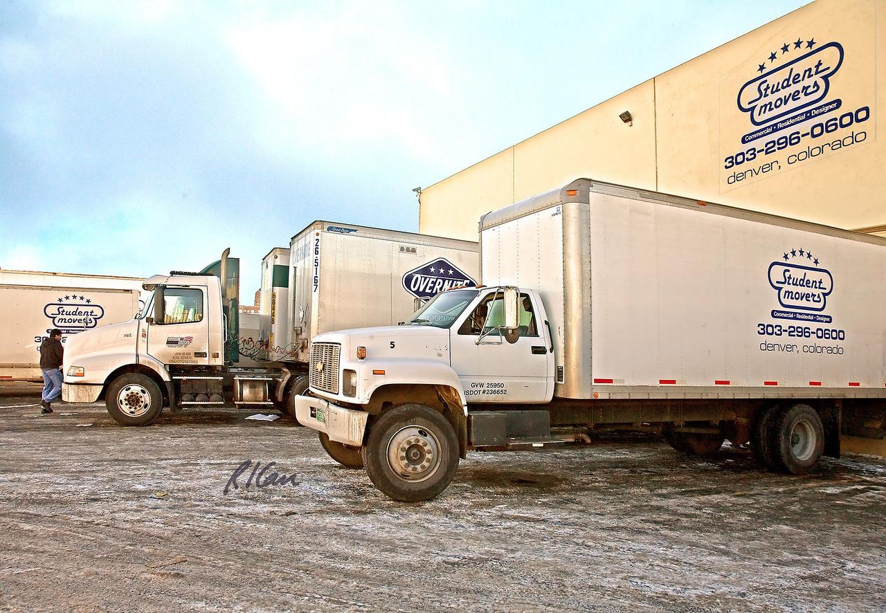 Trucks, hauling: Moving trucks backed up to individual loading docks/gates for loading/unloading.
