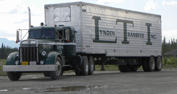 June 25, 2011:  Riding through Tok, AK one afternoon, I spotted this old Kenworth pulling out of the parking lot of Fast Eddy's restaurant.  Recognizing it as an historic vehicle, I asked the driver for some details.  This is what I got from him, and some internet research:  This is one of the two, specially built Kenworths LTI purchased in 1954 to begin trucking over the Alcan Highway.  The first load was 36,000 lbs of swinging beef, delivered to the Carrs store in Fairbanks.   This tractor had been located by LTI and restored to look like new again.  It was powered by a 240 horsepower Cummins diesel, with a 5 speed main and 4 speed auxiliary transmission.  Either this truck. or its sister truck, is seen in a collection of photos, 6th row down, at:  http://tinyurl.com/3sswrgr with the rear wheels of the trailer over the inside edge of a curve north of Quesnel, B.C.