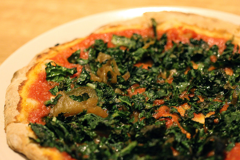 Tomato and kale pizza with carmelized onions