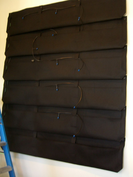 A six-high stack of modular Woolly Pockets, already fitted with drip-irrigation tubing and ready to be planted.