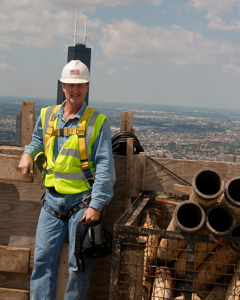 Me, on the 85th floor with my camera bag.     What am I, the manager of software development for Prairie, doing up here?  No--I'm not auditioning for The Village People.  The great people in the Prairie QC department know of both my photography hobby and my prior life as a concrete worker, and have gotten me a pass to go up into many of the skyscrapers we pour during their construction.  It's a great way to get a rare view of the city!