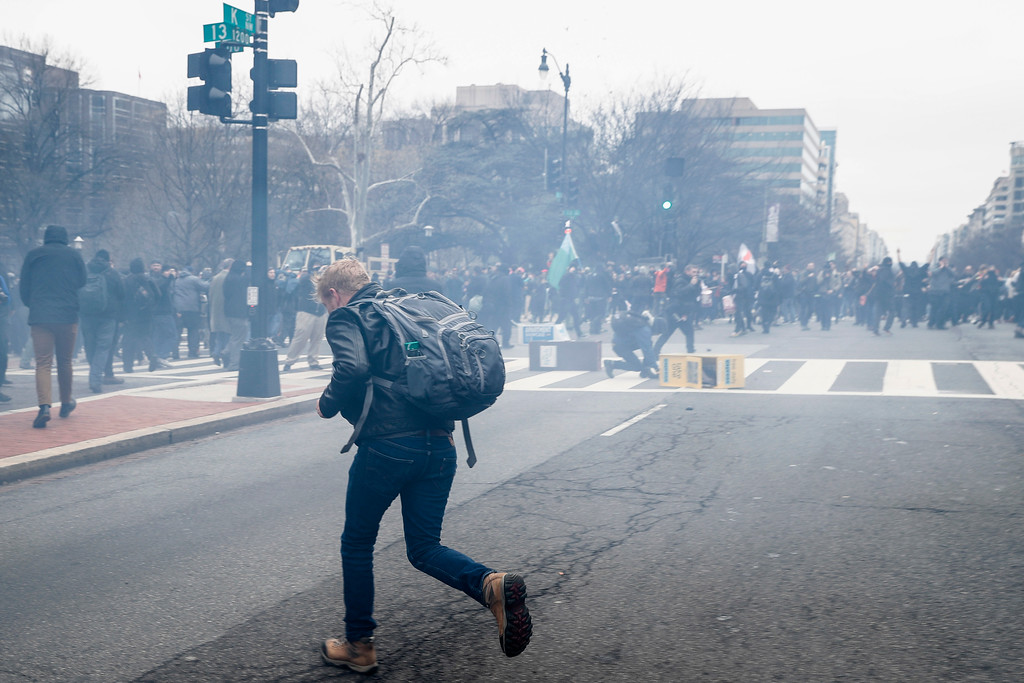 . A protester runs to escape a cloud of tear gas fired by police forces during a demonstration after the inauguration of President Donald Trump, Friday, Jan. 20, 2017, in Washington. (AP Photo/John Minchillo)
