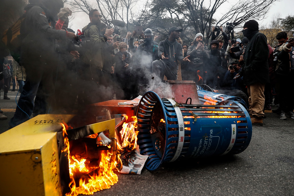 . A Washington resident, center right, demands peace as he guards a pile of burning newspaper machines to prevent protestors from feeding the flames during a demonstration after the inauguration of President Donald Trump, Friday, Jan. 20, 2017, in Washington. (AP Photo/John Minchillo)