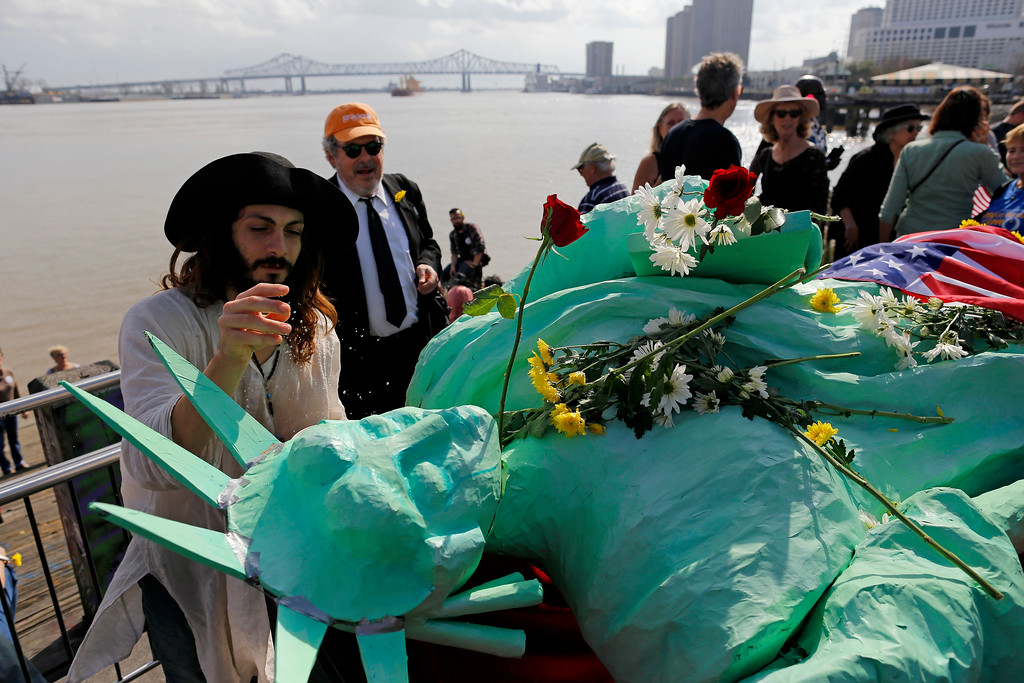 . Sebastian Knight, left, plashes water on a Statue of Liberty sculpture in a sign of hopeful rebirth after a mock jazz funeral was held in protest the inauguration of Donald Trump in New Orleans, Friday, Jan. 20, 2017. Donald J. Donald J. Trump was sworn in as the 45th President of the United States today. (AP Photo/Max Becherer)