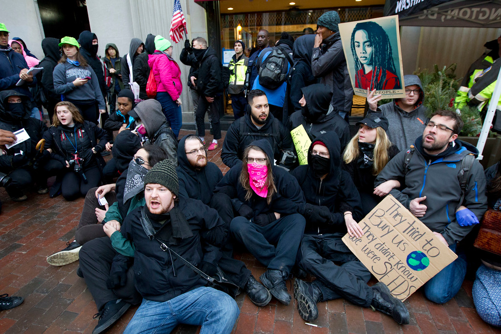 . Demonstrators sit on sidewalk attempting to block people entering a security checkpoint, Friday, Jan. 20, 2017, ahead of President-elect Donald Trump\'s inauguration in Washington. ( AP Photo/Jose Luis Magana)
