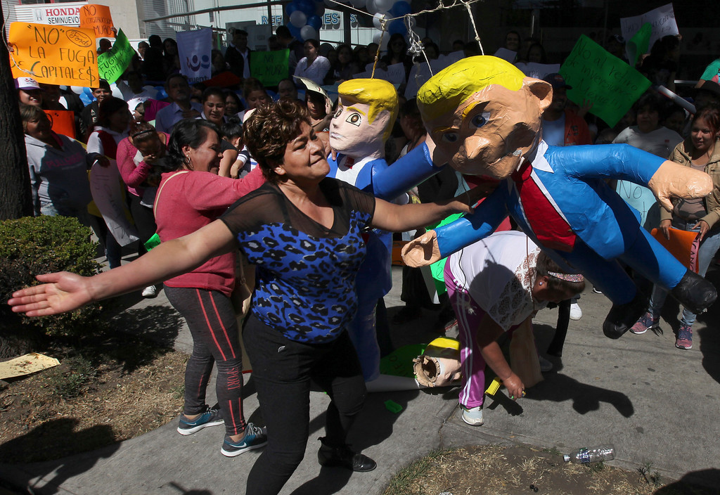 . Women smack a pinata likeness of U.S. President Donald Trump in Mexico City, Friday, Jan. 20, 2017. Donald Trump became the 45th president of the United States Friday, Jan. 20 2017, amid apprehension in Mexico regarding his previous comments about Mexico and his promise to build a border wall to halt migration. (AP Photo/Marco Ugarte)