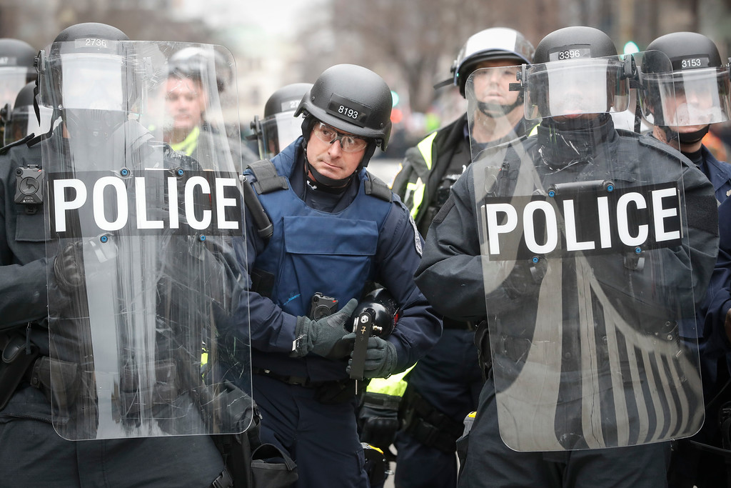 . A police officer carrying a pepper spray gun stands between riot shields during a demonstration after the inauguration of President Donald Trump, Friday, Jan. 20, 2017, in Washington. (AP Photo/John Minchillo)