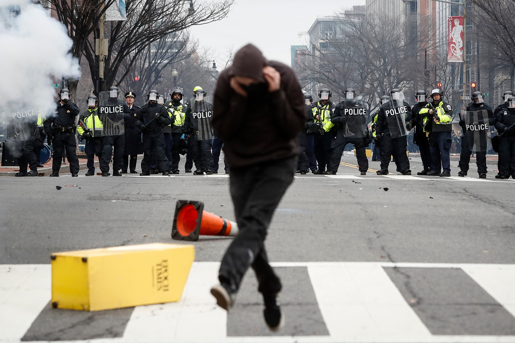 . A protester runs from a flash bang grenade fired by police forces during a demonstration after the inauguration of President Donald Trump, Friday, Jan. 20, 2017, in Washington. (AP Photo/John Minchillo)