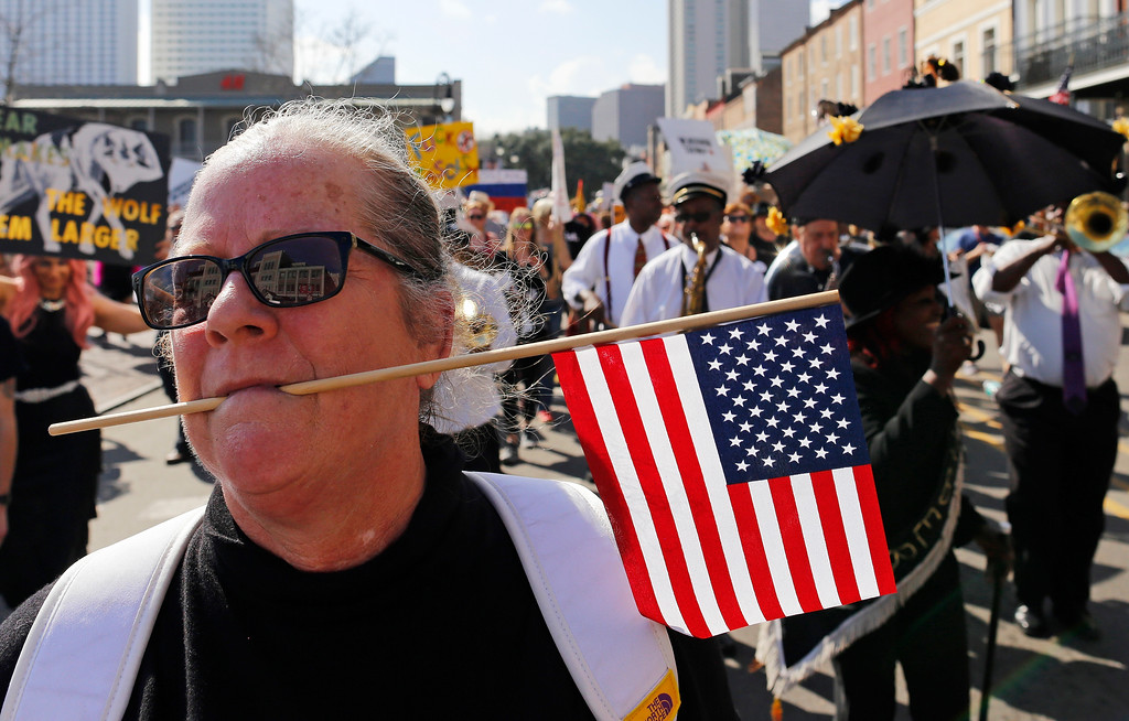 . Lara Batchelder dances with a U.S. flag in her mouth during a protest against the inauguration of Donald Trump in New Orleans, Friday, Jan. 20, 2017. Donald J. Trump was sworn in as the 45th President of the United States today. (AP Photo/Max Becherer)