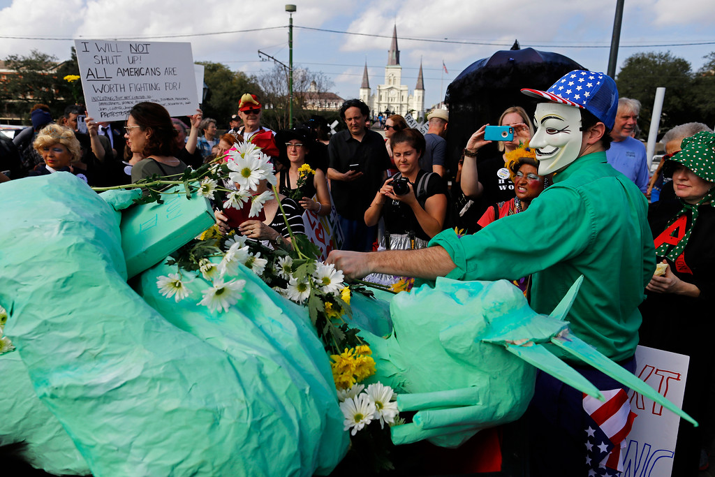 . Protesters lay flowers on a Statue of Liberty sculpture laying in a coffin in a protest of the inauguration of Donald Trump in New Orleans, Friday, Jan. 20, 2017. Donald J. Trump was sworn in as the 45th President of the United States today. (AP Photo/Max Becherer)