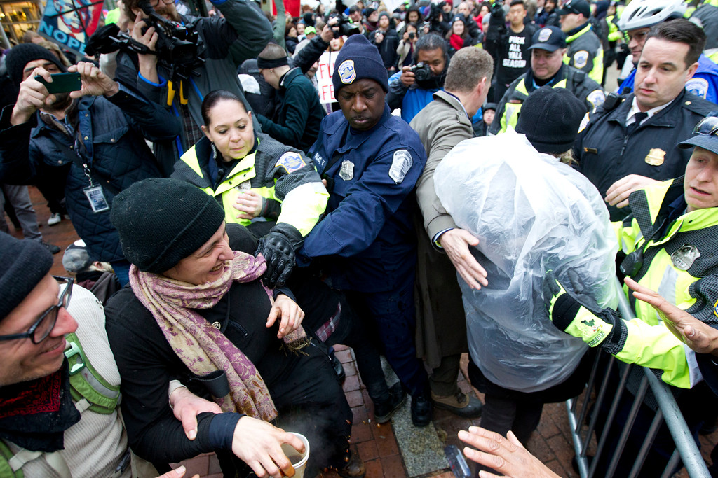 . Police officers push back demonstrators attempting to block people entering a security checkpoint, Friday, Jan. 20, 2017, ahead of President-elect Donald Trump\'s inauguration in Washington. ( AP Photo/Jose Luis Magana)