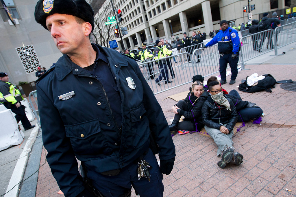 . Demonstrators sit near a security checkpoint as police officers let people pass to the inauguration, Friday, Jan. 20, 2017 in Washington, ahead of President-elect Donald Trump\'s inauguration. ( AP Photo/Jose Luis Magana)