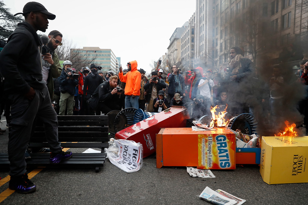 . A Washington resident, left, guards a pile of burning newspaper machines to prevent protestors from feeding the flames while demanding peace in the streets during a demonstration after the inauguration of President Donald Trump, Friday, Jan. 20, 2017, in Washington. (AP Photo/John Minchillo)