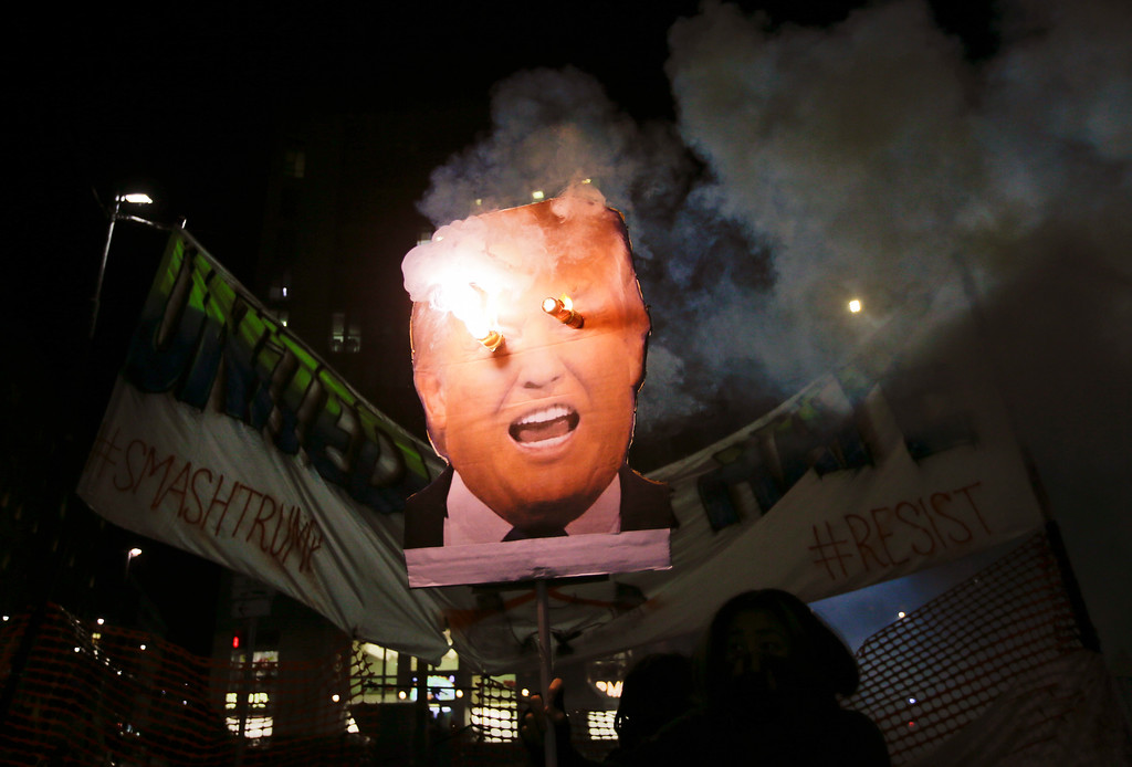 . Flares burn on a picture of U.S. President Donald Trump during a protest in front of the U.S. Consulate in Milan, Italy, Friday, Jan. 20, 2017. (AP Photo/Luca Bruno)
