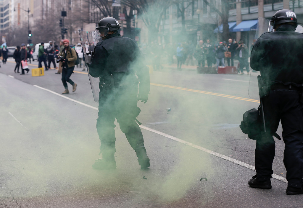 . Protesters throw smoke devices at police during clashes in northwest Washington, Friday, Jan. 20, 2017. (AP Photo/Mark Tenally)