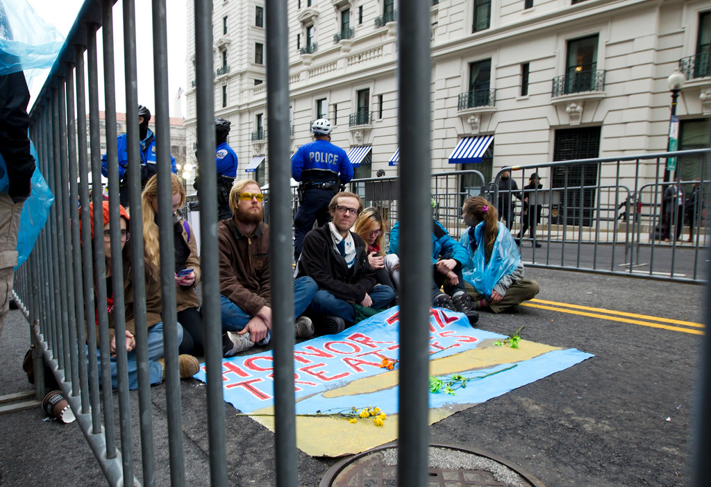 . Demonstrators sit at the entrance of a security checkpoint, to block people to enter, Friday, Jan. 20, 2017, during the inauguration of President Donald Trump in Washington. ( AP Photo/Jose Luis Magana)