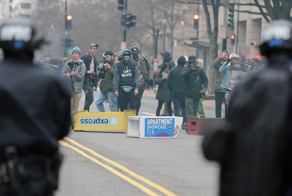 . Protesters face off with police in downtown Washington, Friday, Jan. 20, 2017. (AP Photo/Mark Tenally)