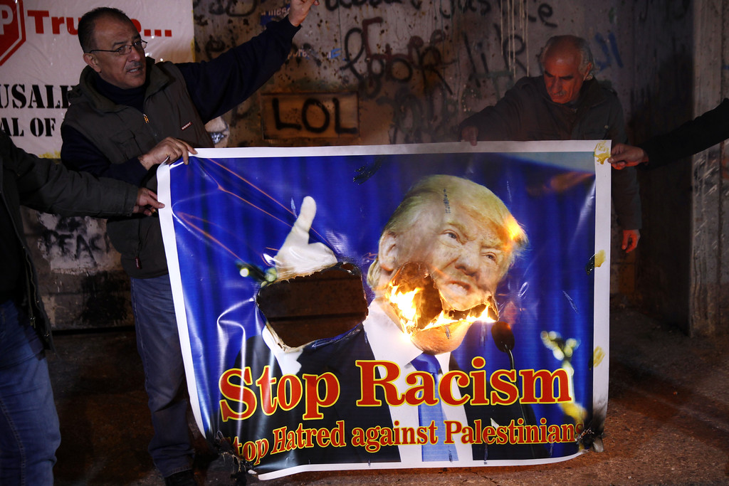 . Palestinians burn a poster showing President Donald Trump during a protest in the west bank city of Bethlehem. Friday, Jan. 20, 2017. (AP Photo/Mahmoud Illean)