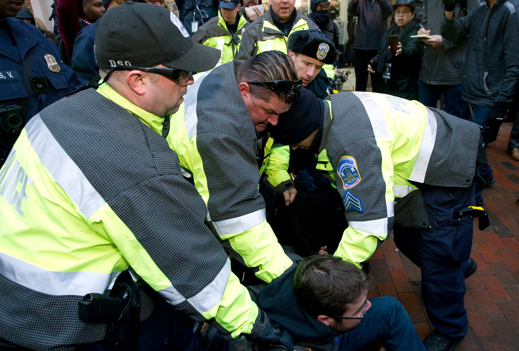 . Police try to remove a demonstrator from attempting to block people entering a security checkpoint, Friday, Jan. 20, 2017, ahead of President-elect Donald Trump\'s inauguration in Washington. ( AP Photo/Jose Luis Magana)