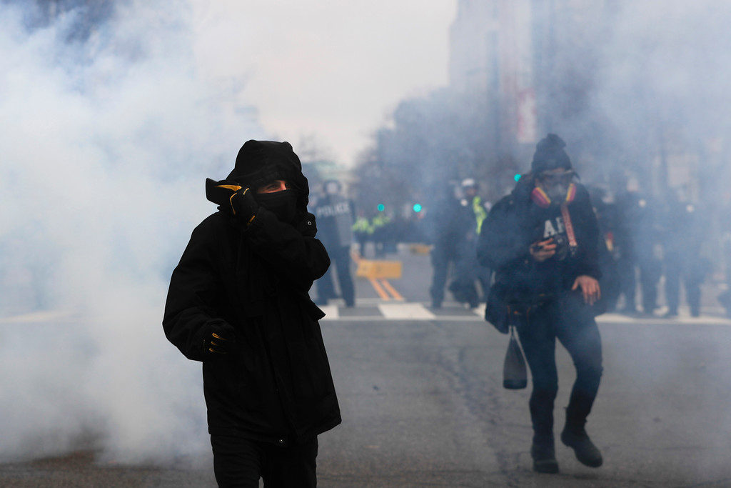 . A protester shields his mouth and nose from gas fired by police during a demonstration after the inauguration of President Donald Trump, Friday, Jan. 20, 2017, in Washington. (AP Photo/John Minchillo)