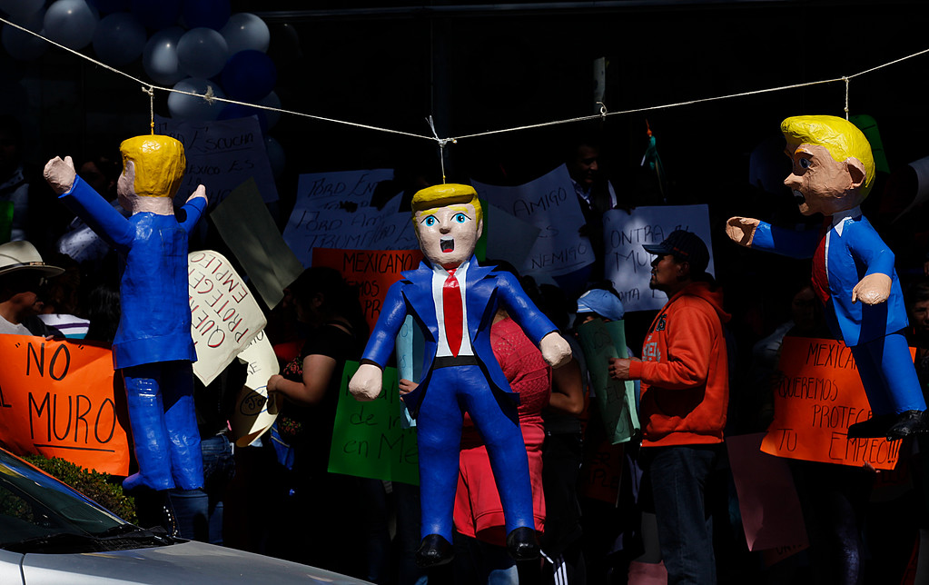 . Pinatas  in the  likeness of U.S. President Donald Trump hang on a length of wire during a protest in Mexico City, Friday, Jan. 20, 2017. Donald Trump became the 45th president of the United States Friday, Jan. 20 2017, amid apprehension in Mexico regarding his previous comments about Mexico and his promise to build a border wall to halt migration. (AP Photo/Marco Ugarte)