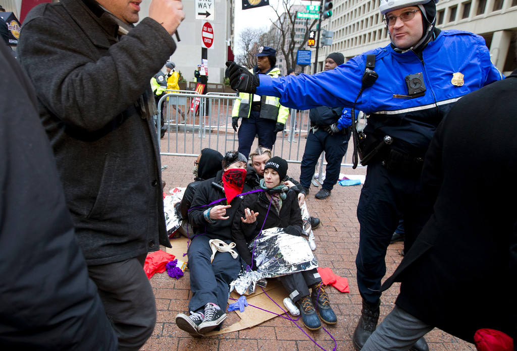 . Demonstrators sit at one of the entrance as police officer let people pass let to the inauguration in Washington, Friday, Jan. 20, 2017, ahead of the President-elect Donald Trump inauguration. ( AP Photo/Jose Luis Magana)