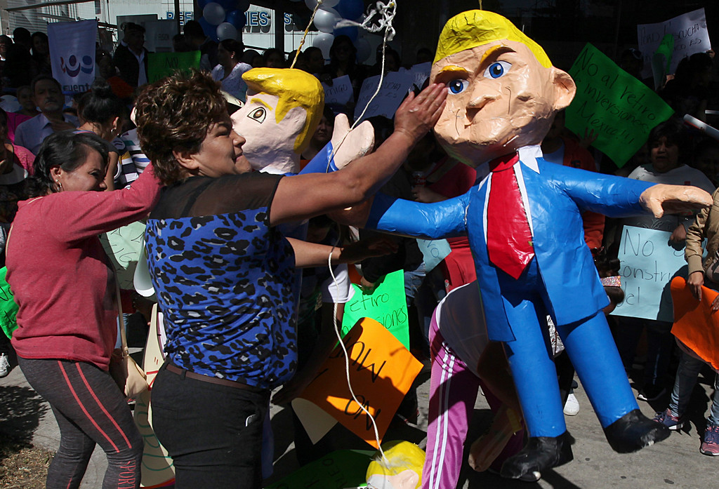 . Women smack pinatas in the likeness of U.S. President Donald Trump in Mexico City, Friday, Jan. 20, 2017. Donald Trump became the 45th president of the United States Friday, Jan. 20 2017, amid apprehension in Mexico regarding his previous comments about Mexico and his promise to build a border wall to halt migration. (AP Photo/Marco Ugarte)
