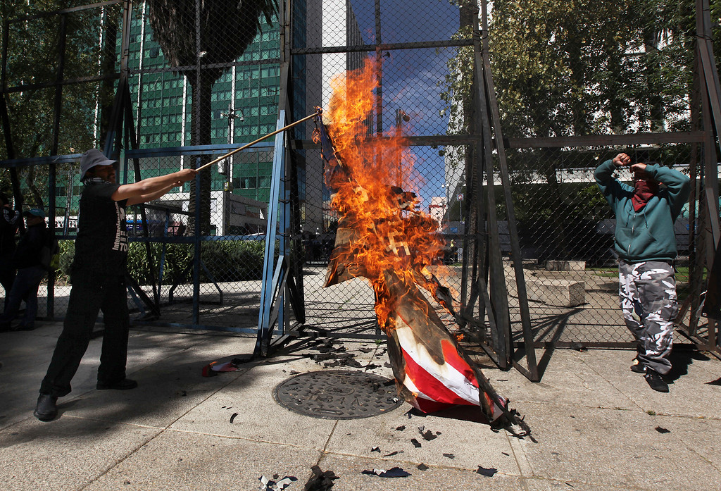 . Protesters burn a mock American flag in front of the U.S. Embassy in Mexico City, Friday, Jan. 20, 2017. Donald Trump became the 45th president of the United States Friday, Jan. 20 2017, amid apprehension in Mexico regarding his previous comments about Mexico and his promise to build a border wall to halt migration. (AP Photo/Marco Ugarte)