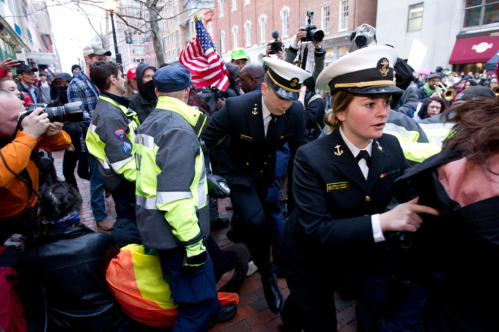 . Navy officers move through demonstrators as police push back to let people get in to the inauguration gate at 10th and E Streets in Washington, Friday, Jan. 20, 2017, ahead of the President-elect Donald Trump inauguration. ( AP Photo/Jose Luis Magana)