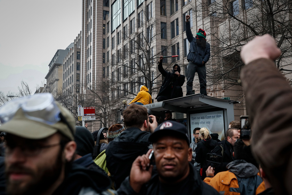 . Protesters raise their fists atop of a bus shelter during a demonstration after the inauguration of President Donald Trump, Friday, Jan. 20, 2017, in Washington. (AP Photo/John Minchillo)