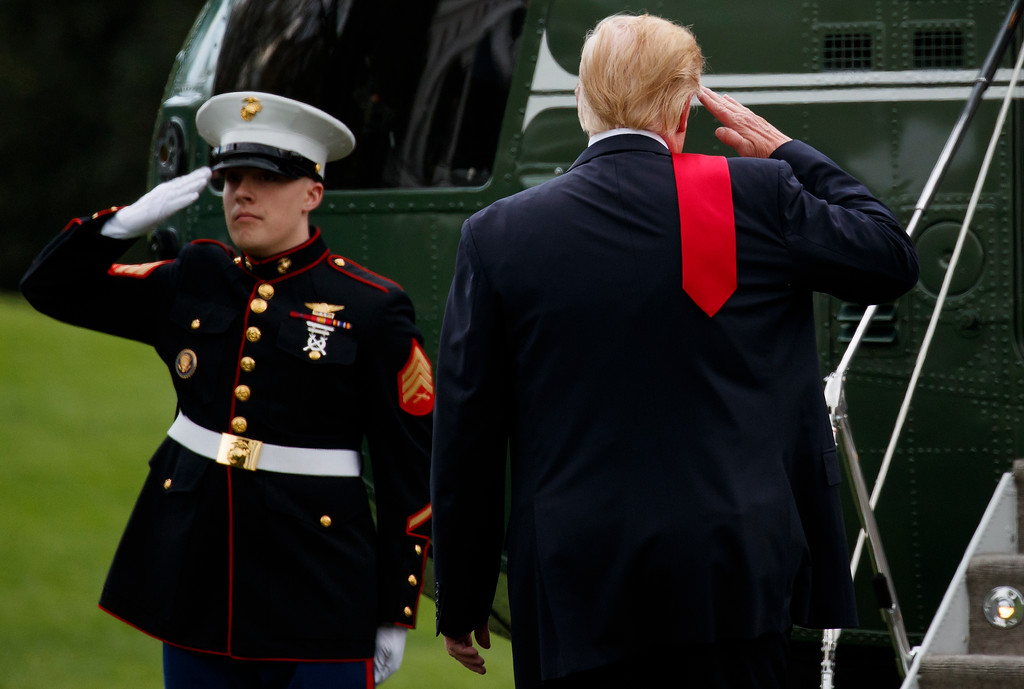. With his red tie over his shoulder, President Donald Trump salutes as he walks to Marine One across the South Lawn of the White House in Washington, Saturday, April 28, 2018, for the short trip to Andrews Air Force Base en route to Michigan. (AP Photo/Carolyn Kaster)