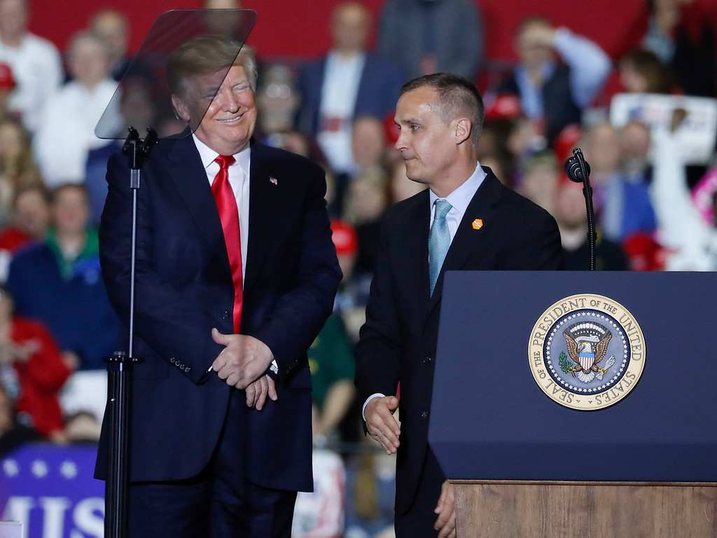 . President Donald Trump, left, smiles after listening to Corey Lewandowski, right, former campaign manager for Trump\'s presidential campaign, make remarks at a rally at Total Sports Park Saturday, April 28, 2018, in Washington, Mich. (AP Photo/Pablo Martinez Monsivais)