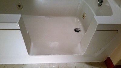 The step has a textured bottom that slopes into the tub at the same angle as the tub bottom .