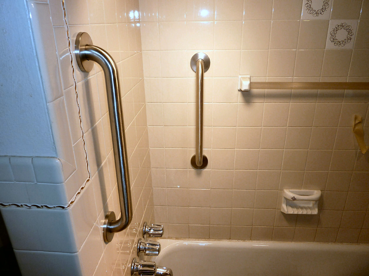 I attached 2 stainless Steel grab bars to the tile, enabling her to steady her entry.