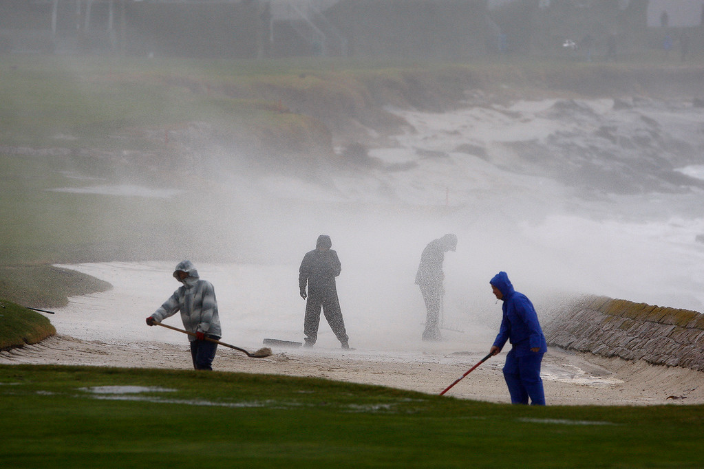 . Greenskeepers get blasted by a wave while working in the wind and rain at the Pebble Beach Golf Links in preparation for the AT&T Pebble Beach Pro Am on Tuesday, Feb. 7, 2017.   (Vern Fisher - Monterey Herald)