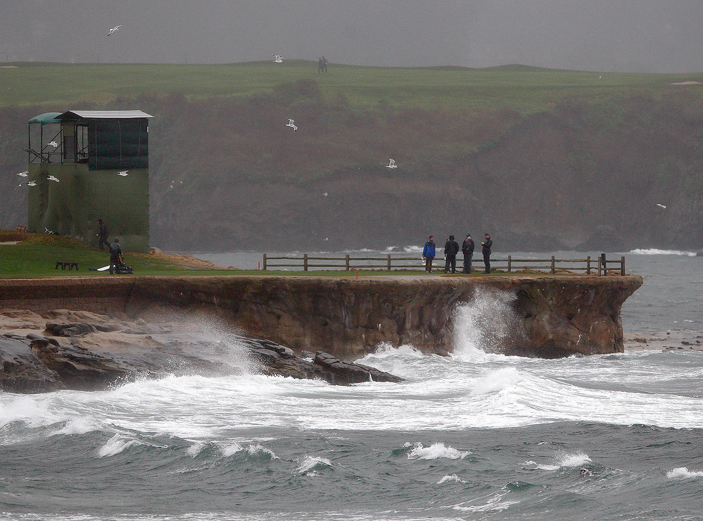 . A group stands on the 18th tee box in the wind and rain at the Pebble Beach Golf Links in preparation for the AT&T Pebble Beach Pro Am on Tuesday, Feb. 7, 2017.   (Vern Fisher - Monterey Herald)