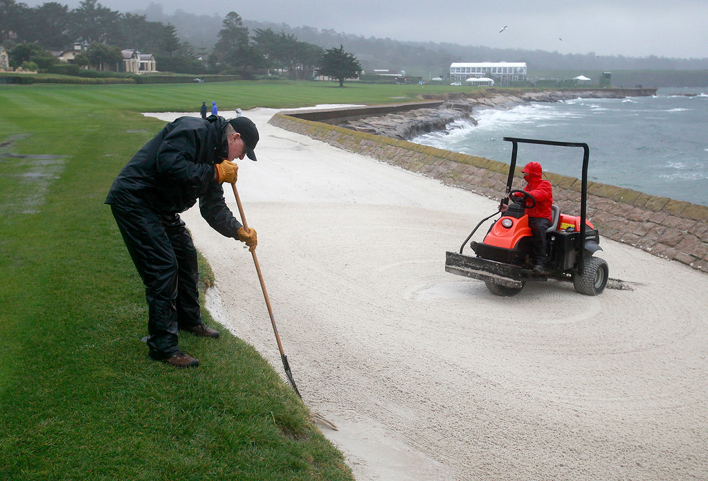 . Volunteer greenskeeper Pete League rakes a bunker on the 18th hole in the wind and rain at the Pebble Beach Golf Links in preparation for the AT&T Pebble Beach Pro Am on Tuesday, Feb. 7, 2017.   (Vern Fisher - Monterey Herald)