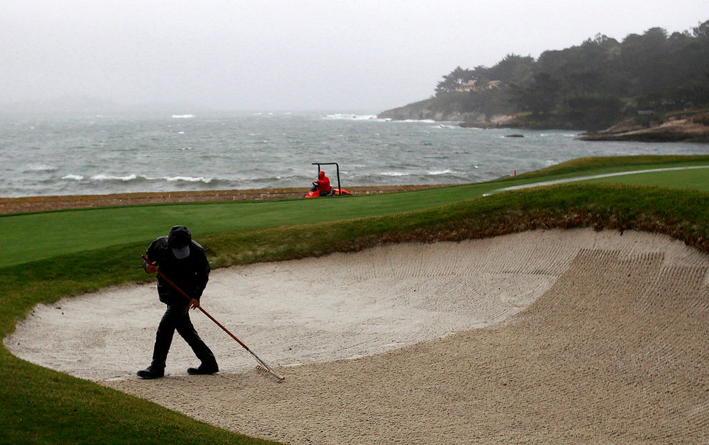 . Greenskeepers work in the wind and rain at the Pebble Beach Golf Links in preparation for the AT&T Pebble Beach Pro Am on Tuesday, Feb. 7, 2017.   (Vern Fisher - Monterey Herald)