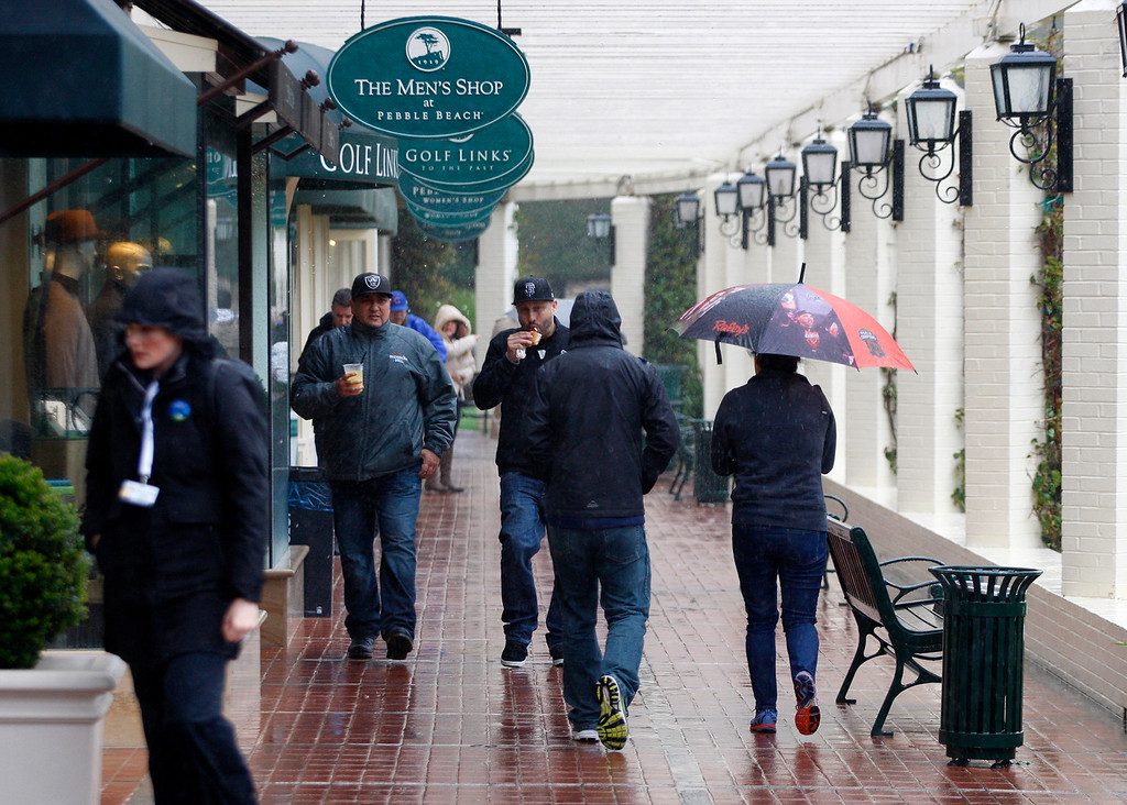 . Patrons battle the wind and rain at the Pebble Beach Golf Links at the AT&T Pebble Beach Pro Am on Tuesday, Feb. 7, 2017.   (Vern Fisher - Monterey Herald)