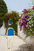 A narrow street with blue and white architecture and bougainvillea flowers in Sidi Bou Said, Tunisia.