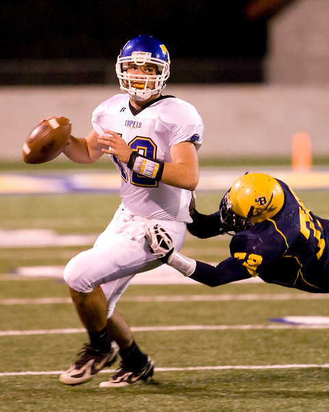 Tupelo QB Chris Garret avoids a tackle by Olive Branch DL Mario Hopkins