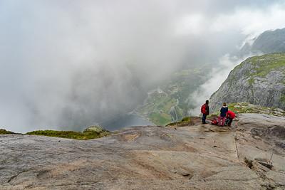 På vei ned fra Kjeragplatået langs en bratt (og i regnvær glatt!) rygg, med utsikt mot Lysebotn.