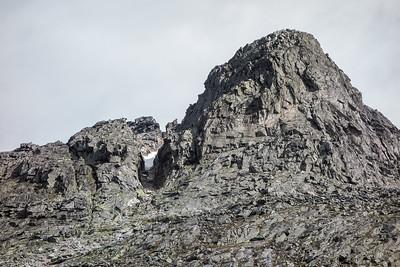 Larstind, med kløften og hovedtoppen, sett fra stien langs vannet nedenfor