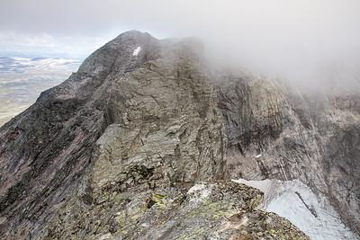 Hettpiggen sett fra Vesttoppen. Skal man gjennomføre Snøhetta-traversen fra øst til vest, er det en lang rapell ned fra Hettpiggen.