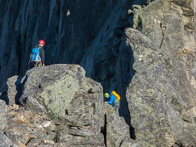 Nedstigning mot det laveste punktet på traversen mellom de to toppene. Noen velger å rappellere ned her (det er satt inn en borebolt for dette), mens andre klyver ned.