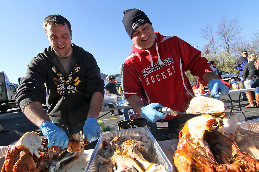 . Catania Oils family members, David Basile and Joseph Basile, crave up some of the first deep fried turkeys for the company annual employee feast. SUN/David H. Brow