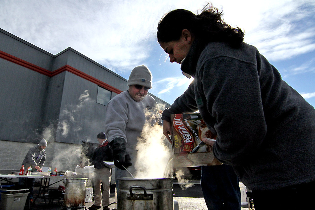 . Lisa Basile, family member that owns Catania Oils, pours in peanut oil into a pot that Kevin Cyr just placed in a turkey for the companies annual turkey feast. SUN/David H. Brow