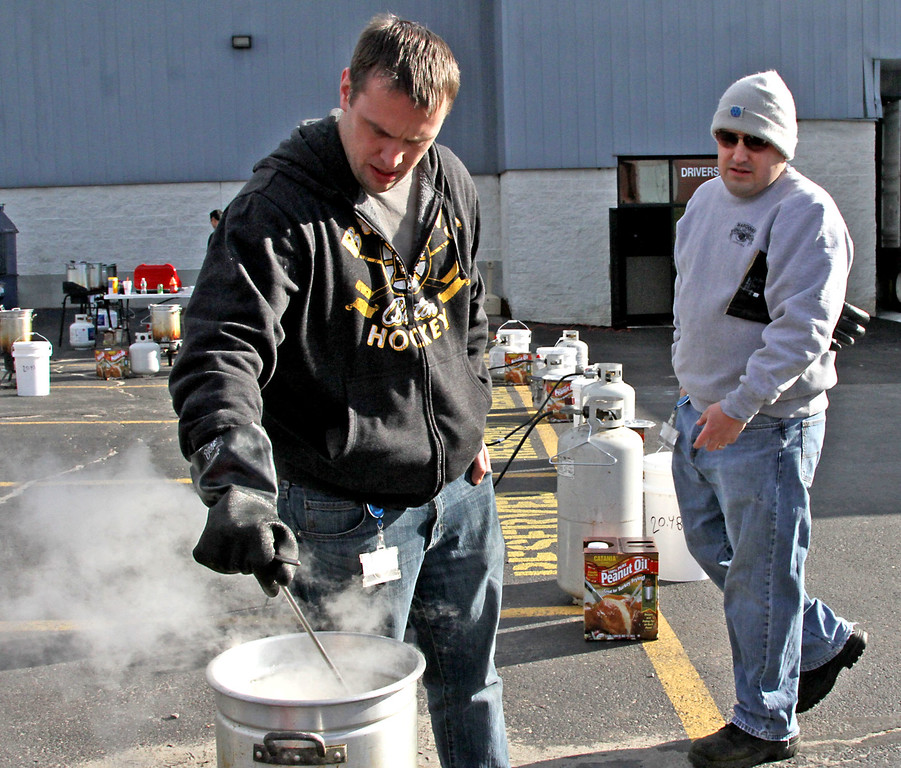 . Checking the temp of the hot peanut oil that will deep fry a turkey, is David Basile of Catania Oils of Ayer, next to him is Kevin Cyr Head Chef at Catania Oil. SUN/David H. Brow
